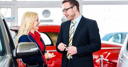 woman buying new car in auto dealership